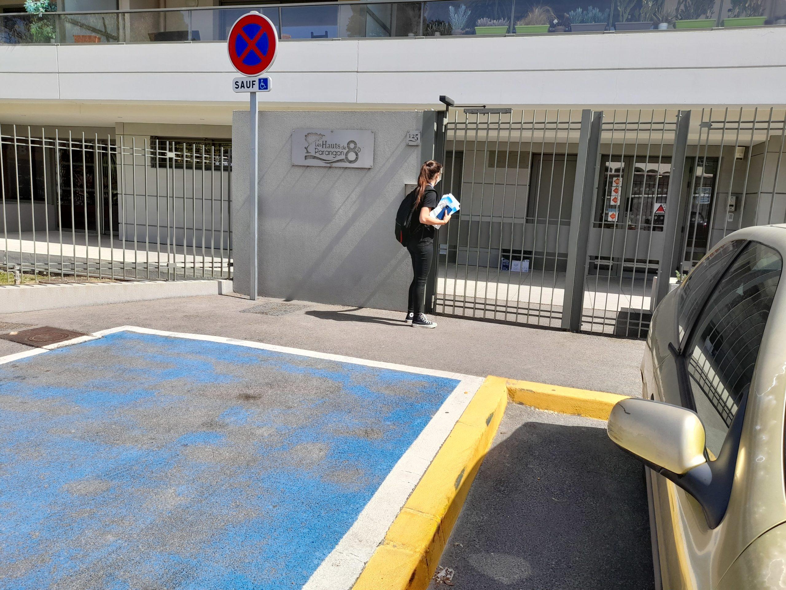 Distribution d'imprimés Marseille hôtesse devant un portail d'un résidence