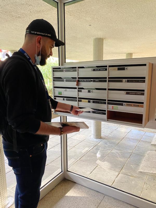 Distribution d'imprimés Marseille Distributeur en train de mettre en boites aux lettres dans un immeuble