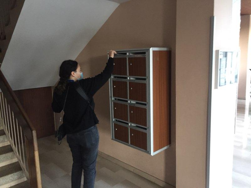 Distribution d'imprimés Marseille hôtesse en train de mettre dans une boites aux lettre dans un immeuble