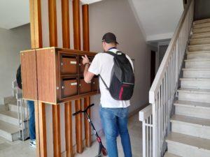 Hote distribuant un cedex de boites aux lettres dans un hall d'entrée d'immeuble