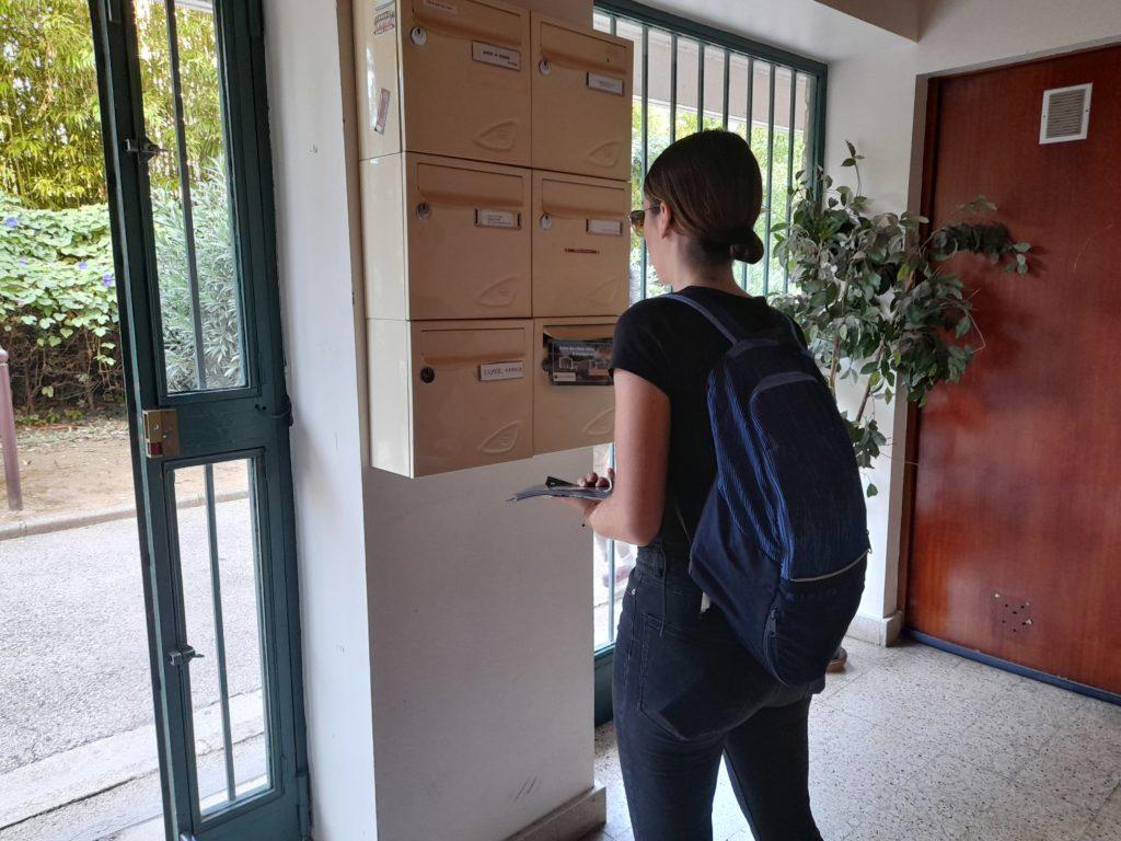 hôtesse en train de distribuer dans un hall d'immeuble sur la Ciotat