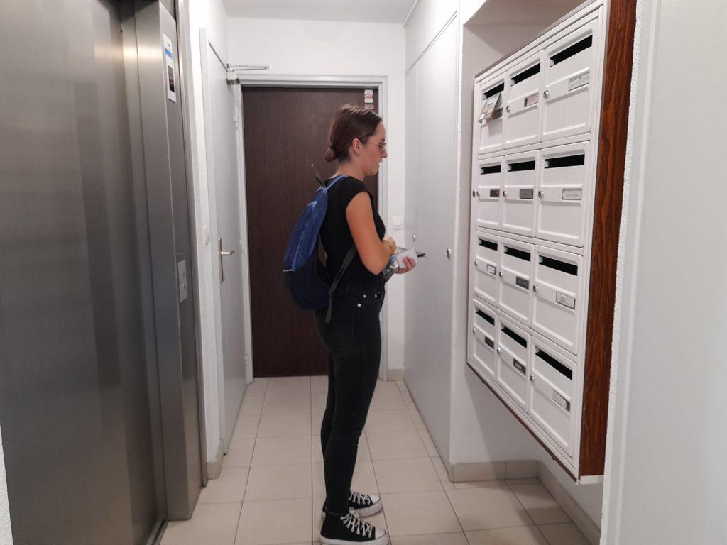 hôtesse en train de mettre en boites aux lettres dans un hall d'immeuble