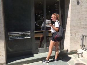 Hôtesse devant l'entrée d'un immeuble attendant l'ouverture