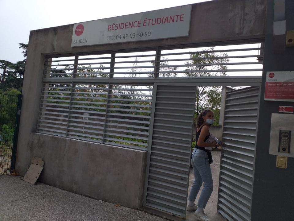 hôtesse devant portail d'entré résidence etudiant