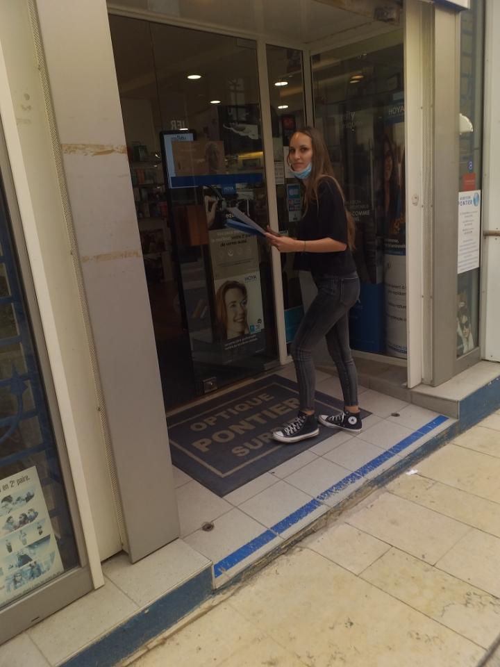 Hôtesse en train d'entrer dans un commerce de la Ciotat pour demander au commerçant l'autorisation de poser une affiche sur sa vitrine